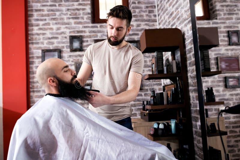 Peluquero que hace el corte de pelo de la barba fotos de archivo