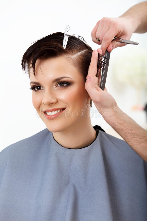 Peluquero que hace el peinado Morenita con el pelo corto en salón fotos de archivo
