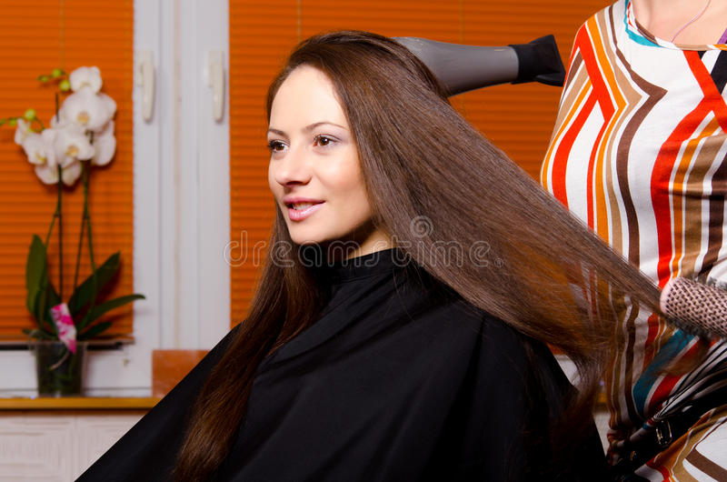 Peluquero que hace el pelo de muchacha feliz hermosa foto de archivo