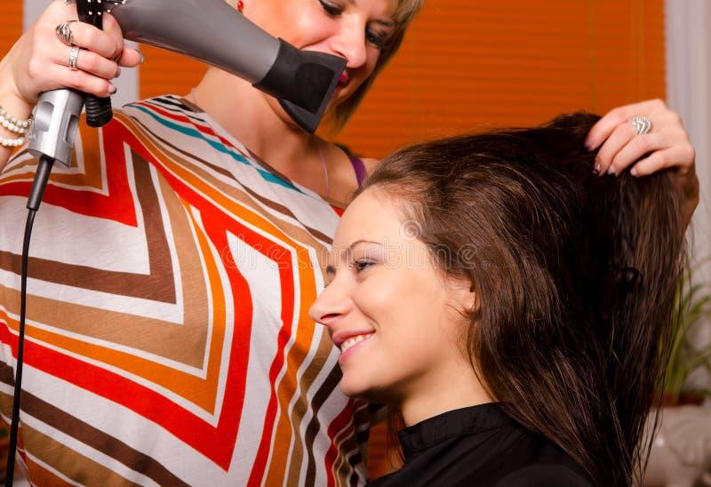 Peluquero que hace el pelo de muchacha hermosa fotos de archivo