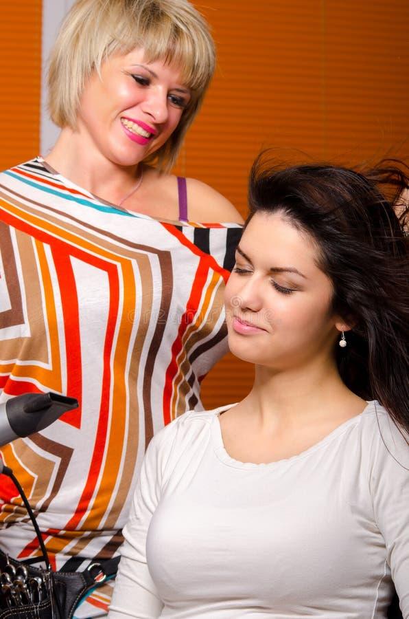 Peluquero que hace el pelo de muchacha hermosa fotografía de archivo