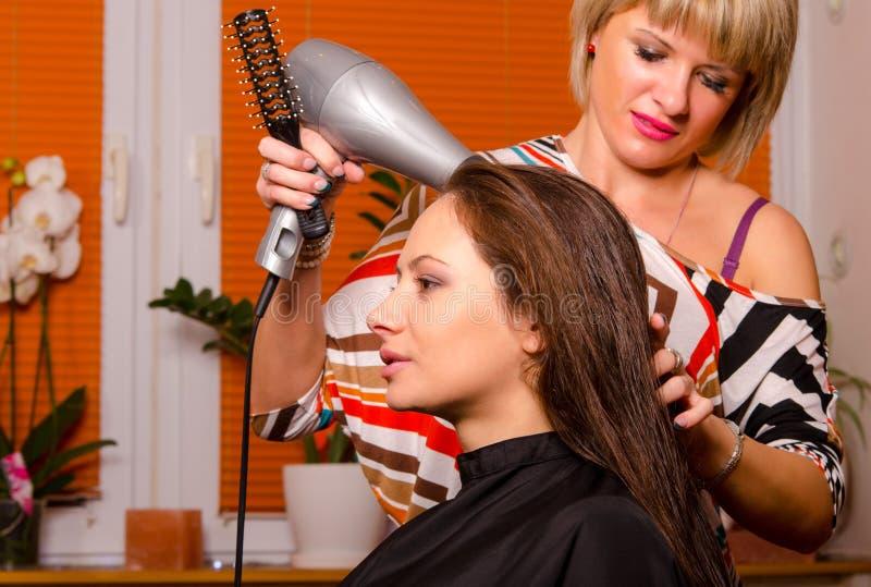 Peluquero que hace el pelo de muchacha hermosa foto de archivo