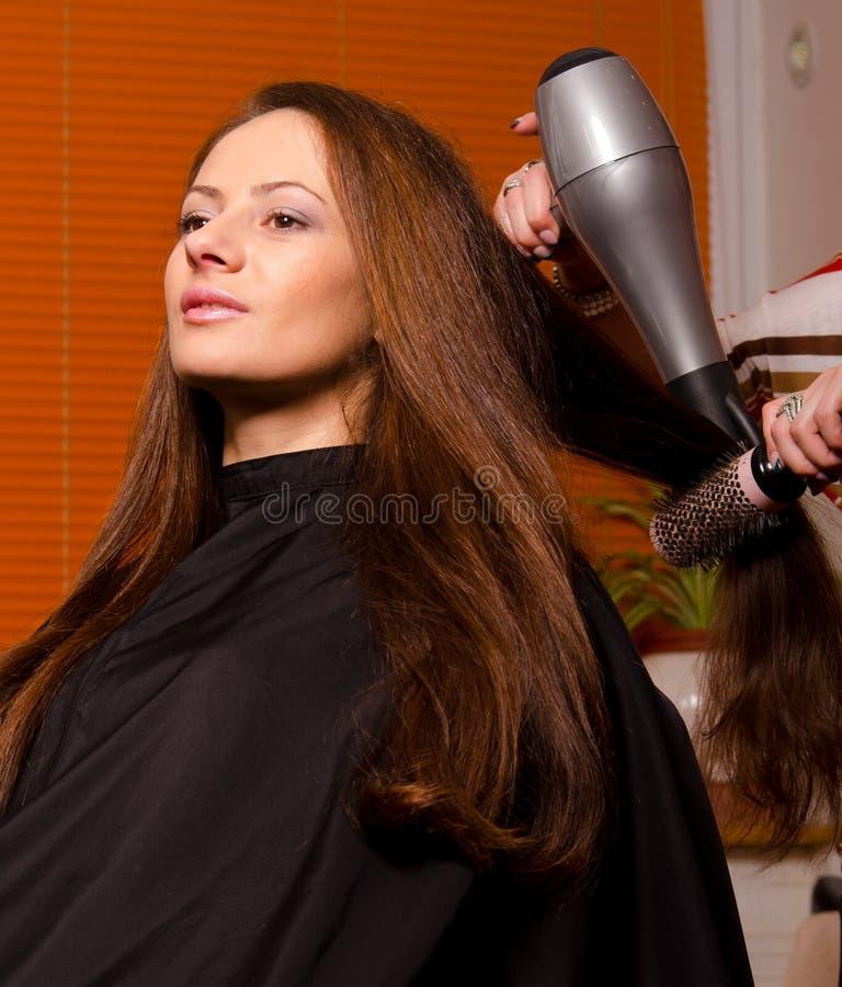 Peluquero que hace el pelo de muchacha hermosa imágenes de archivo libres de regalías