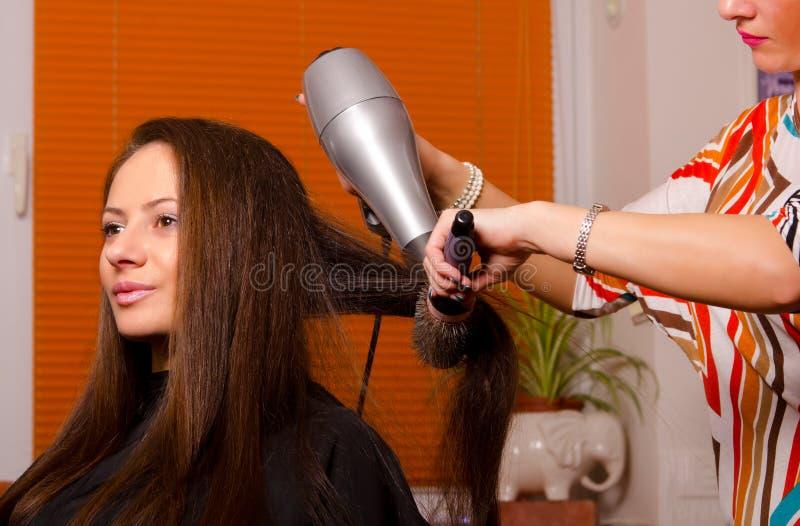 Peluquero que hace el pelo de muchacha hermosa fotografía de archivo libre de regalías