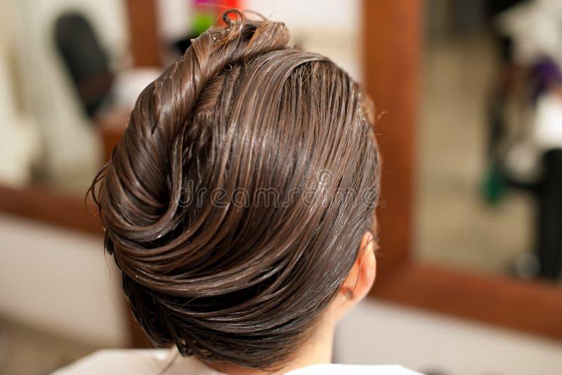 Peluquero que hace el tratamiento del pelo a un cliente en salón fotos de archivo libres de regalías