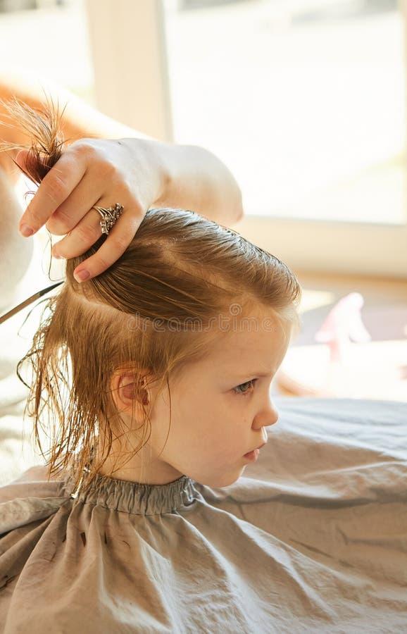 Peluquero que hace un estilo de pelo a la niña linda fotografía de archivo libre de regalías