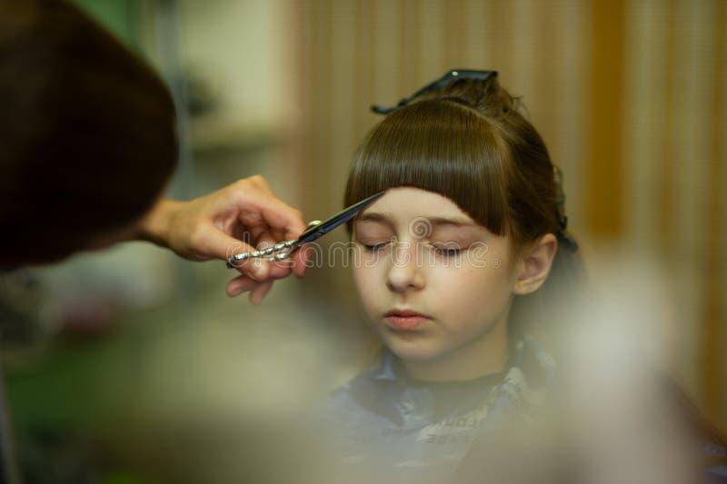 Peluquero que hace un estilo de pelo a la ni?a linda fotografía de archivo libre de regalías