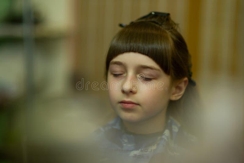 Peluquero que hace un estilo de pelo a la ni?a linda imagen de archivo libre de regalías
