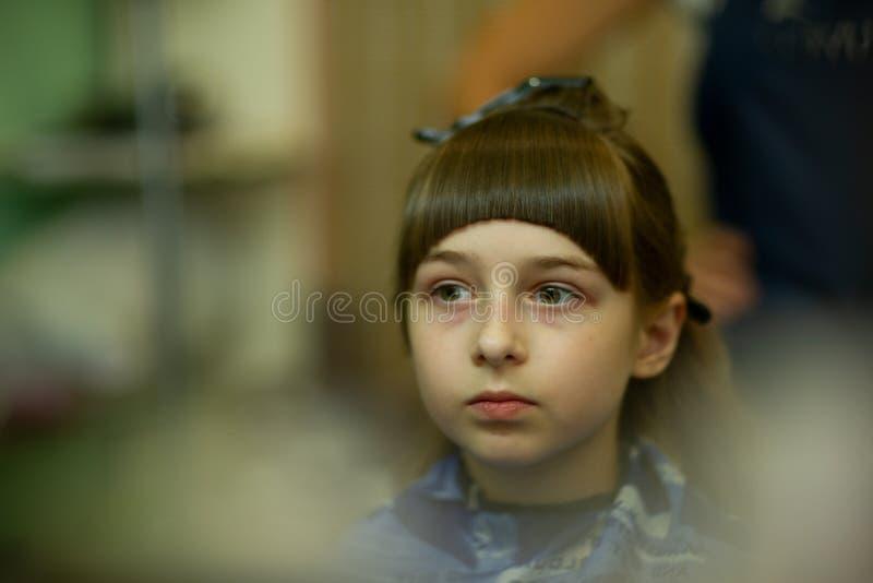 Peluquero que hace un estilo de pelo a la ni?a linda fotos de archivo libres de regalías