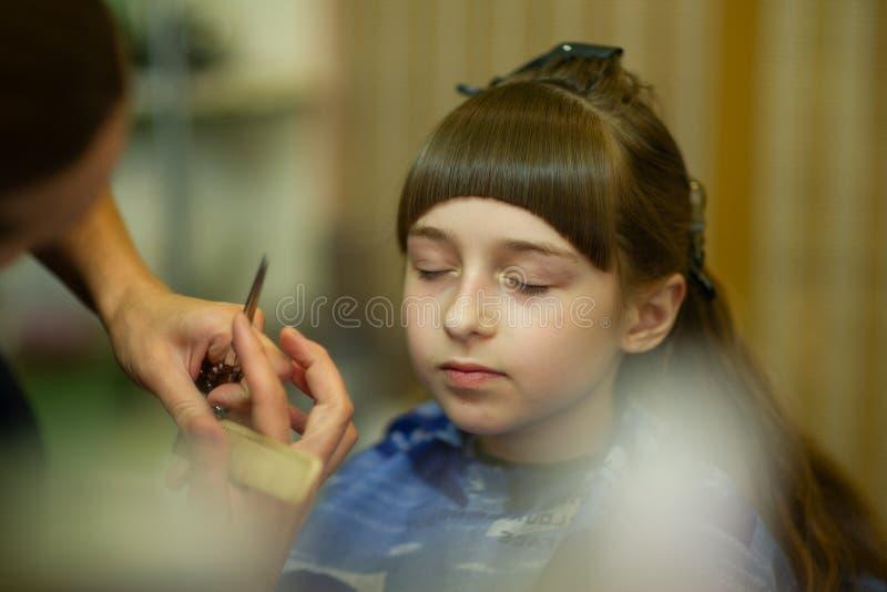 Peluquero que hace un estilo de pelo a la ni?a linda fotos de archivo