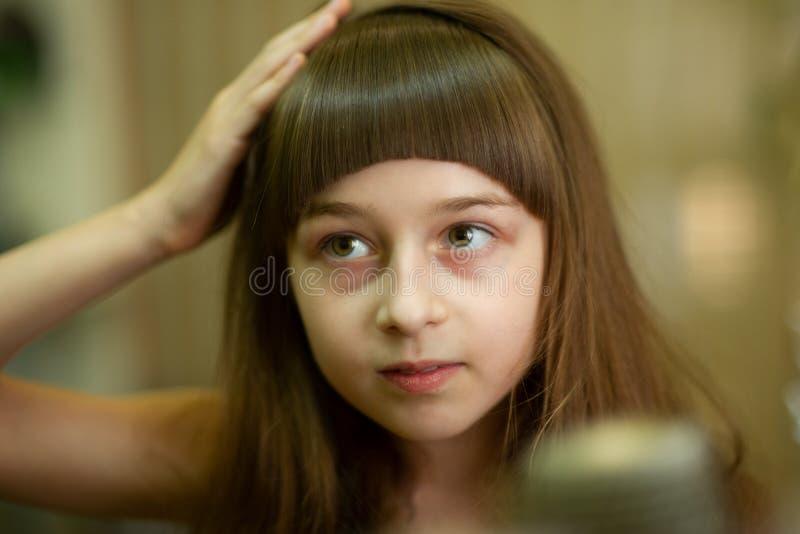 Peluquero que hace un estilo de pelo a la ni?a linda foto de archivo