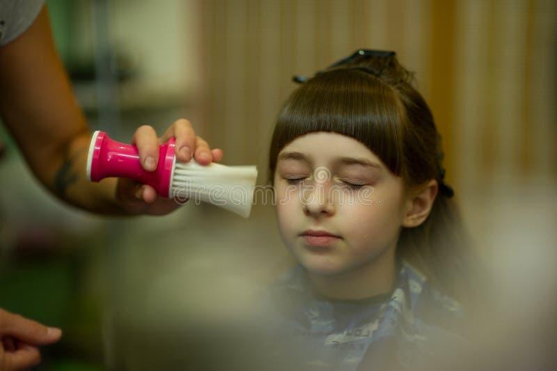 Peluquero que hace un estilo de pelo a la ni?a linda imágenes de archivo libres de regalías