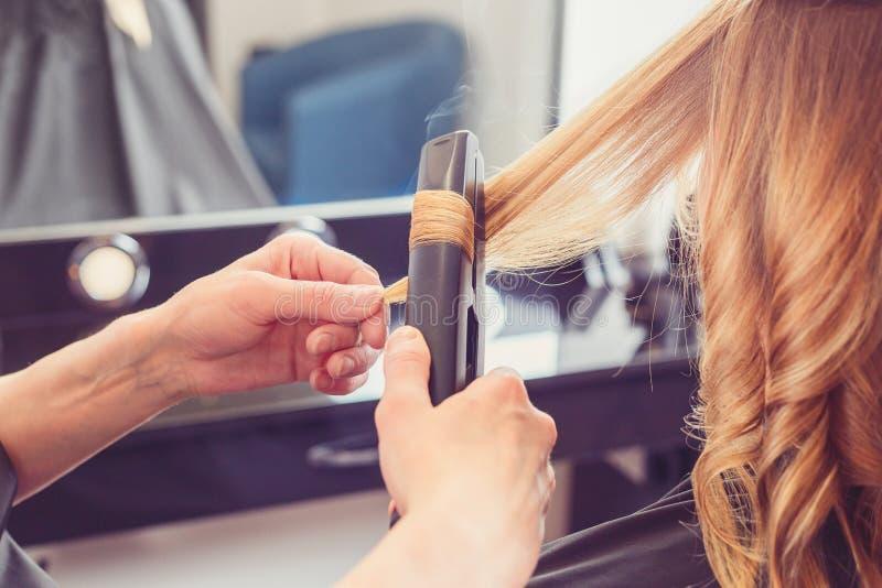 Peluquero que hace un peinado para el cliente imagen de archivo