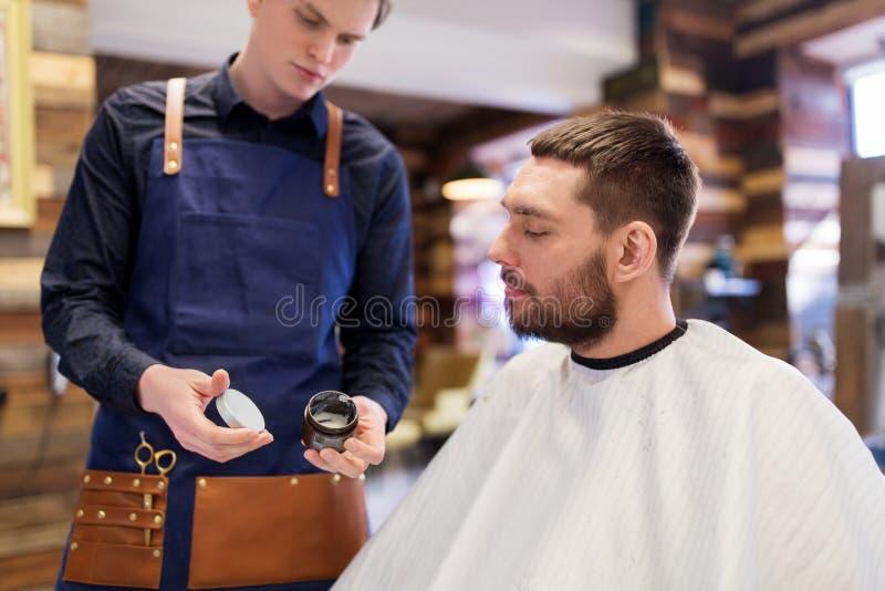 Peluquero que muestra el pelo que diseña la cera al cliente masculino foto de archivo