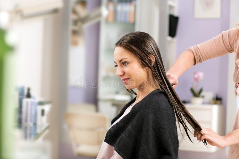 Peluquero que peina el pelo de la mujer en salón fotos de archivo
