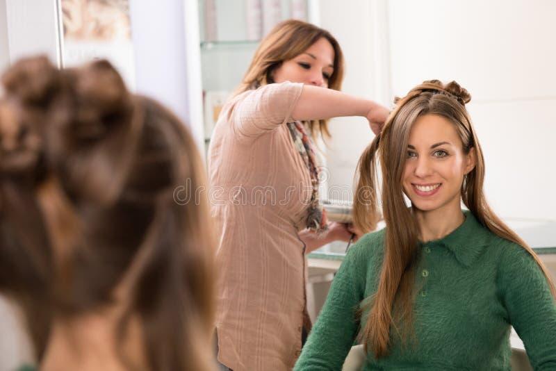 Peluquero que peina el pelo largo de una chica joven fotos de archivo