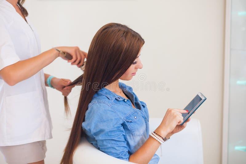Peluquero que peina a la mujer del pelo con el teléfono móvil en peluquería imagen de archivo libre de regalías
