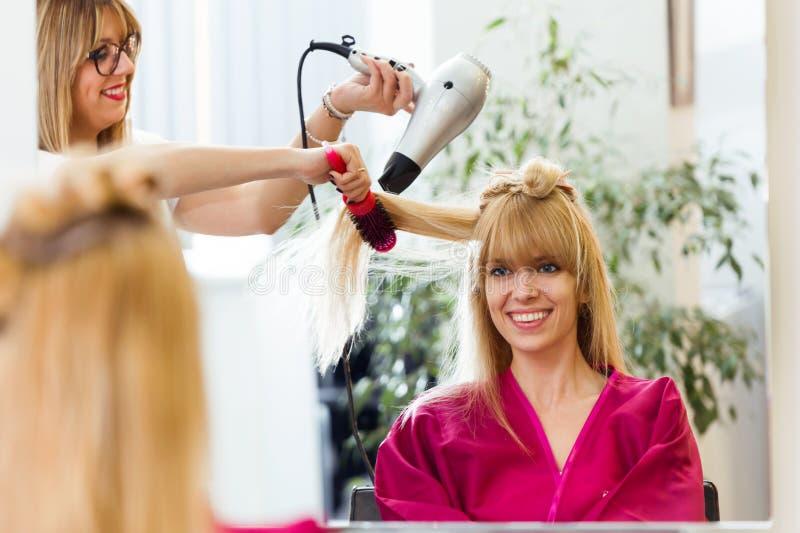 Peluquero que seca el pelo femenino del ` s del cliente en salón de belleza fotos de archivo libres de regalías