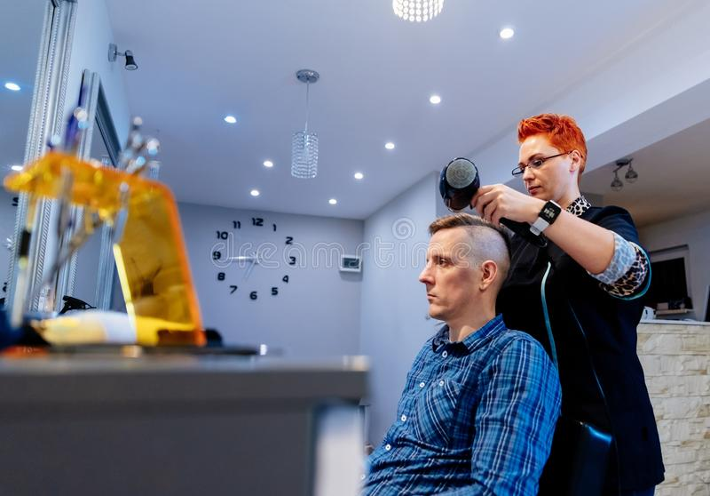 Peluquero que seca el pelo masculino del cliente en salón imagenes de archivo