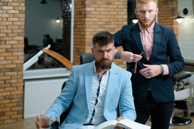 Peluquero que visita del hombre mayor en barbería Peluquero profesional en interior de la barbería La preparación del pelo está a fotografía de archivo