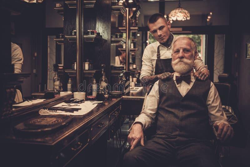 Peluquero que visita del hombre mayor en peluquería de caballeros fotografía de archivo