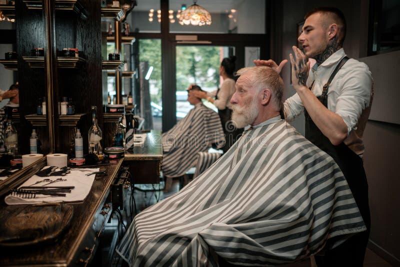 Peluquero que visita del hombre mayor en peluquería de caballeros foto de archivo libre de regalías