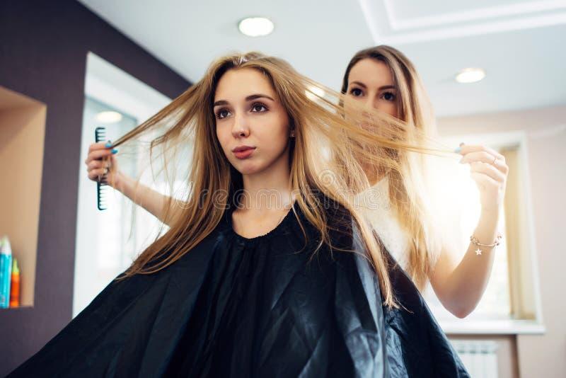 Peluquero y cliente que discuten, decisión, eligiendo cómo cortar el pelo en salón de la peluquería fotografía de archivo
