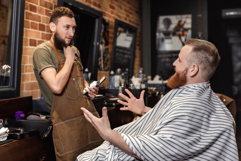 Peluquero y hombre barbudo en peluquería de caballeros fotografía de archivo
