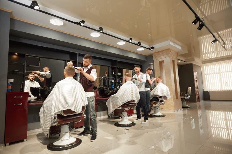 Peluqueros de sexo masculino que mantienen a clientes en peluquería de caballeros foto de archivo libre de regalías