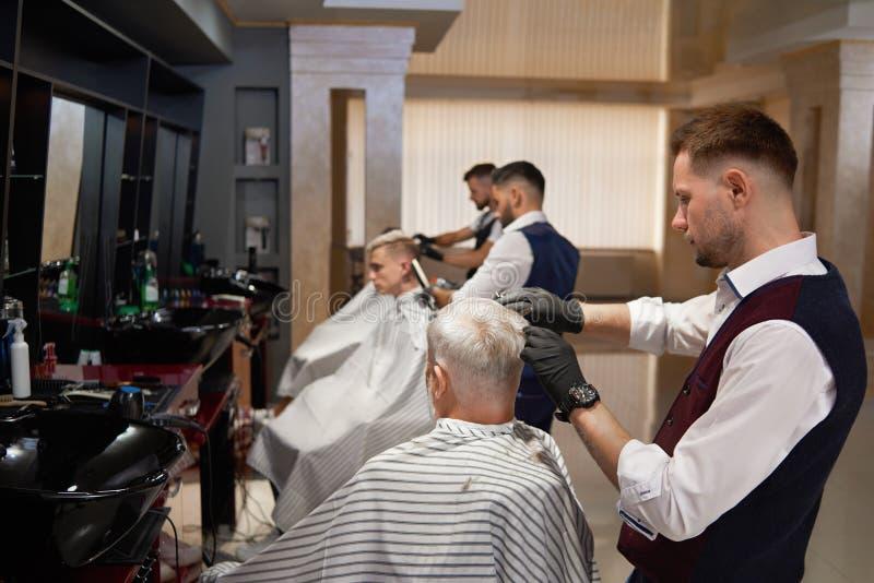 Peluqueros de sexo masculino que preparan cortes de pelo del ` s del cliente en barbería fotografía de archivo