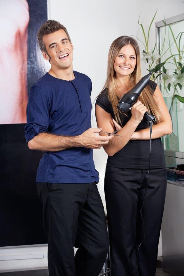 Peluqueros felices que sostienen las tijeras y Hairdryer imagenes de archivo