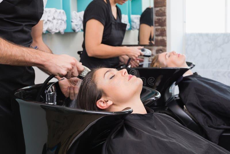 Peluqueros que se lavan el pelo de los clientes imágenes de archivo libres de regalías