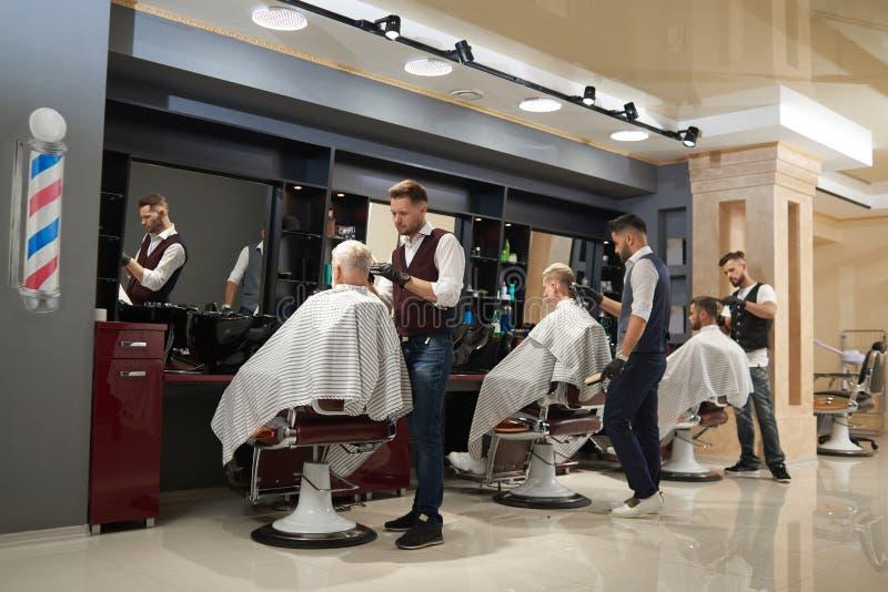 Peluqueros que trabajan con los clientes en barbería moderna imagen de archivo