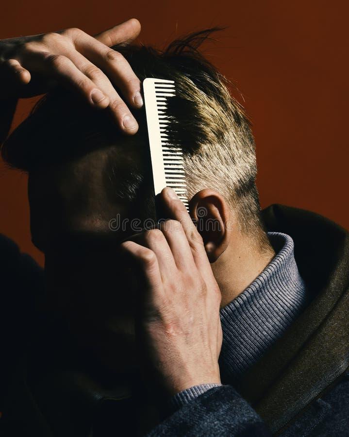 Peluqueros y concepto del estilo Estilista que peina el pelo en fondo rojo Hombre en estilo del vintage foto de archivo libre de regalías