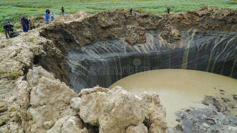 PENÍNSULA DE YAMAL, RUSIA - 18 DE JUNIO DE 2015: Expedición al embudo gigante del origen desconocido Opinión del cráter imagen de archivo libre de regalías