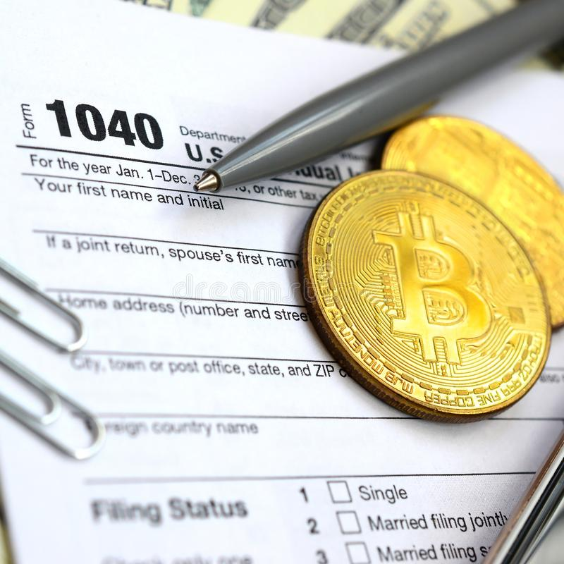 The pen, bitcoins and dollar bills is lies on the tax form 1040 stock photo