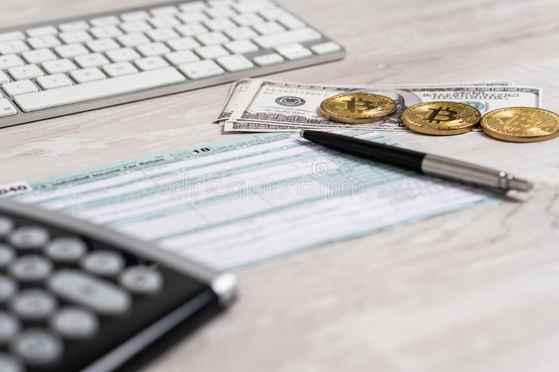The pen, bitcoins, dollar bills and calculator on the tax form 1040 U.S next to computer keyboard. Individual Income Tax stock images