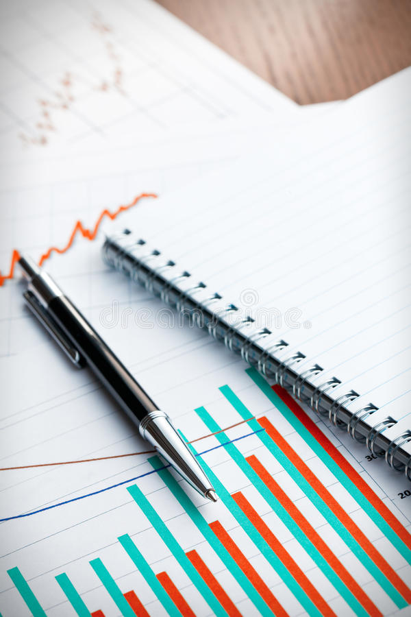 Pen and blank notebook on business graph royalty free stock image
