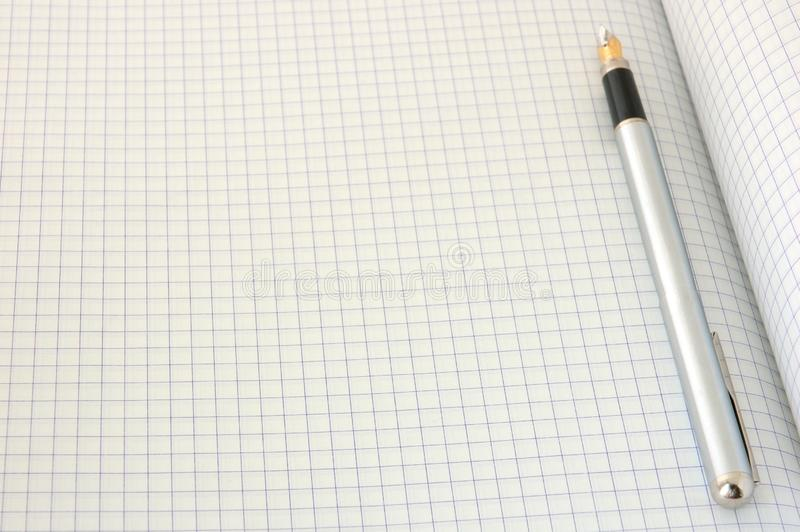 Pen on blank squared paper royalty free stock image