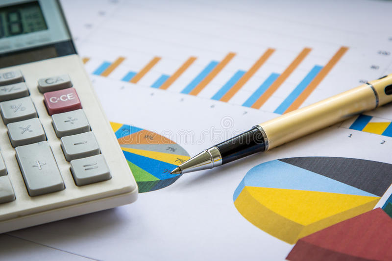 Pen and calculator on graph background royalty free stock photo