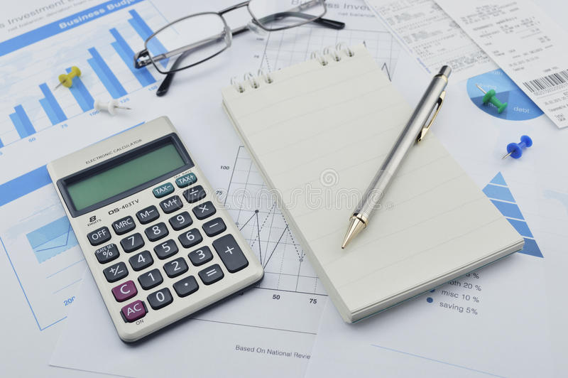 Pen, calculator and notebook on financial chart and graph, accounting background royalty free stock images