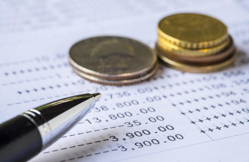 Pen and coins on Bank Account statement. Personal Finance concept. Pen and coins on Bank Account statement stock photo
