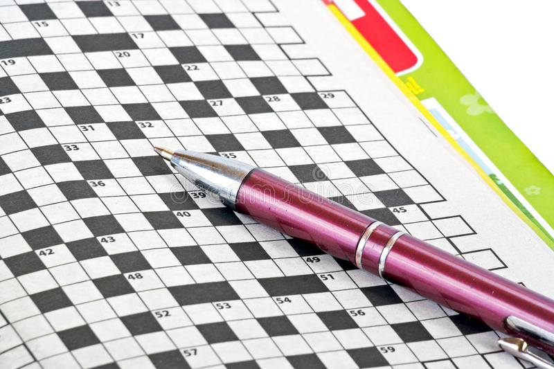 Pen and crossword. Ballpoint pen and a collection of crossword puzzles isolated on white background royalty free stock images