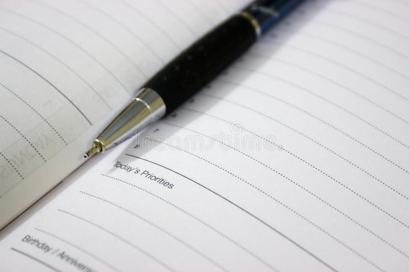 Pen and diary. A pen kept on a diary with white pages listing today's priorities and list of tasks o be done. A yearly planner stock images