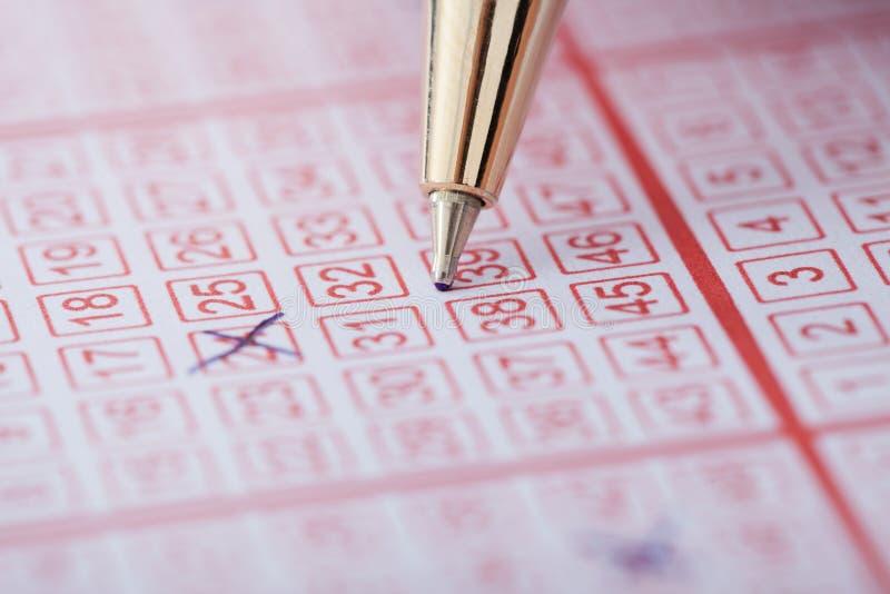 Pen die aantallen op loterijkaartje merken stock foto