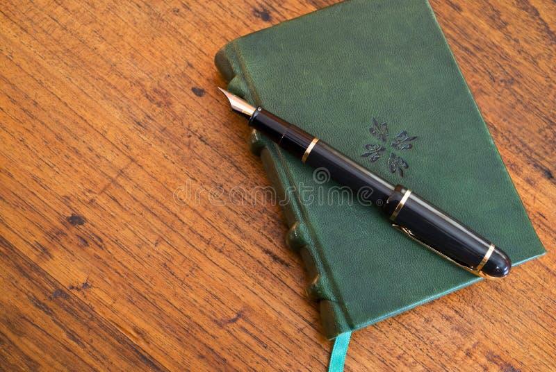 Pen en dagboek op houten bureau royalty-vrije stock afbeeldingen
