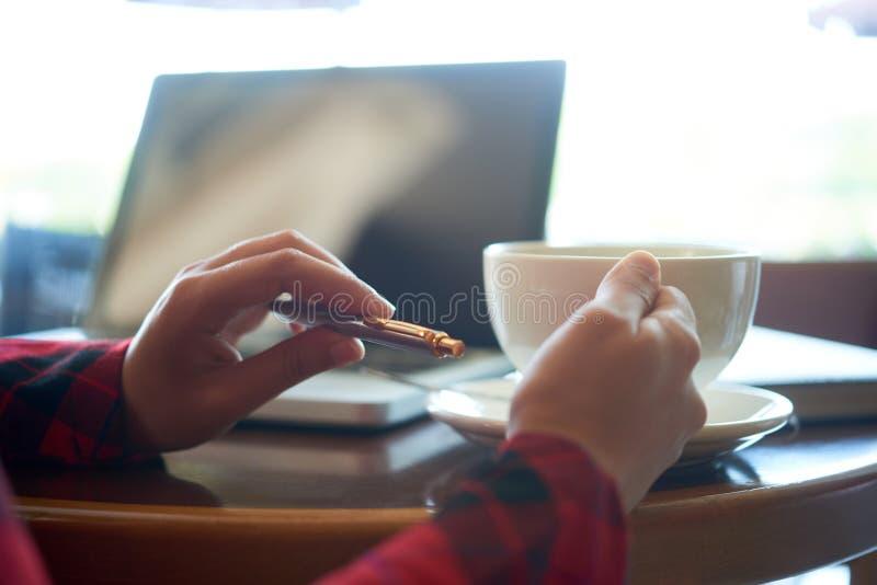 Pen en koffiekop in hads van freelancer royalty-vrije stock foto