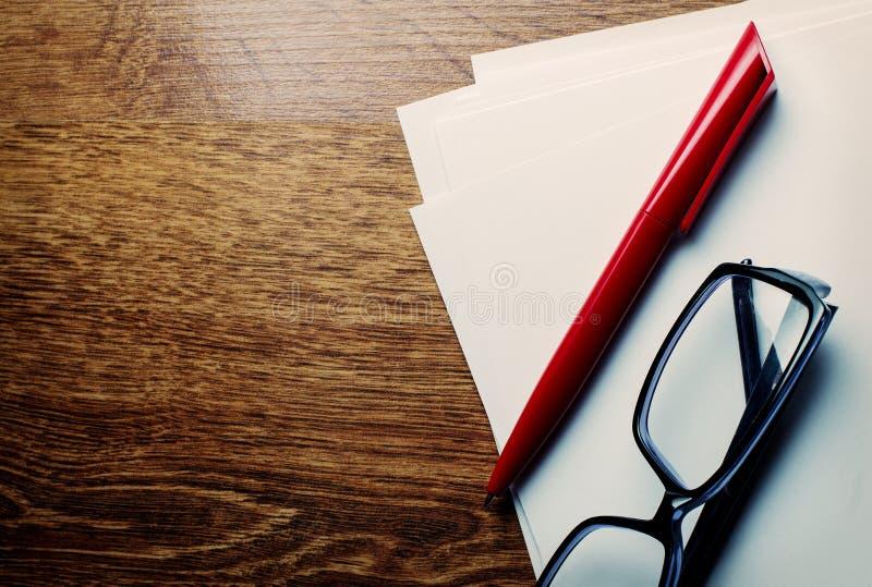 Pen en lezingsglazen op leeg document stock afbeeldingen