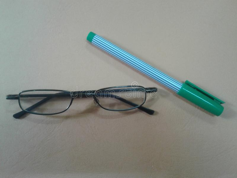 Pen and Eyeglasses on the table. EYE GLASSES and pens on the table and pictures can be used for editorials stock images