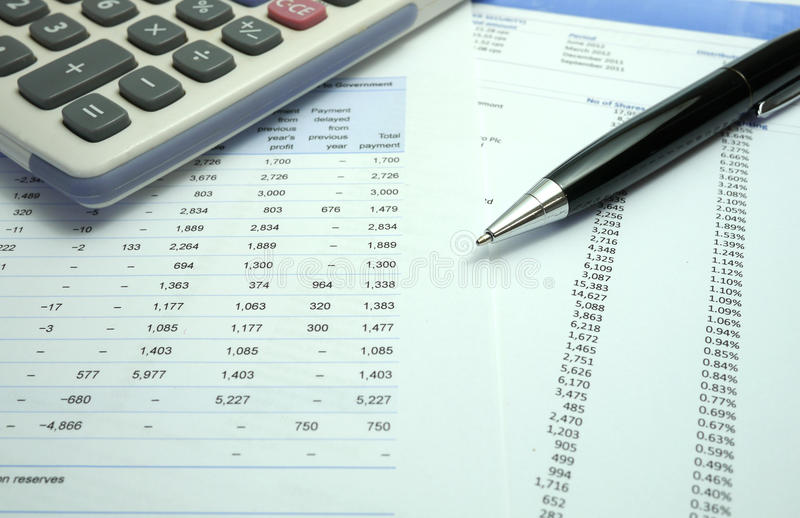 Pen on financial documents with calculator royalty free stock image